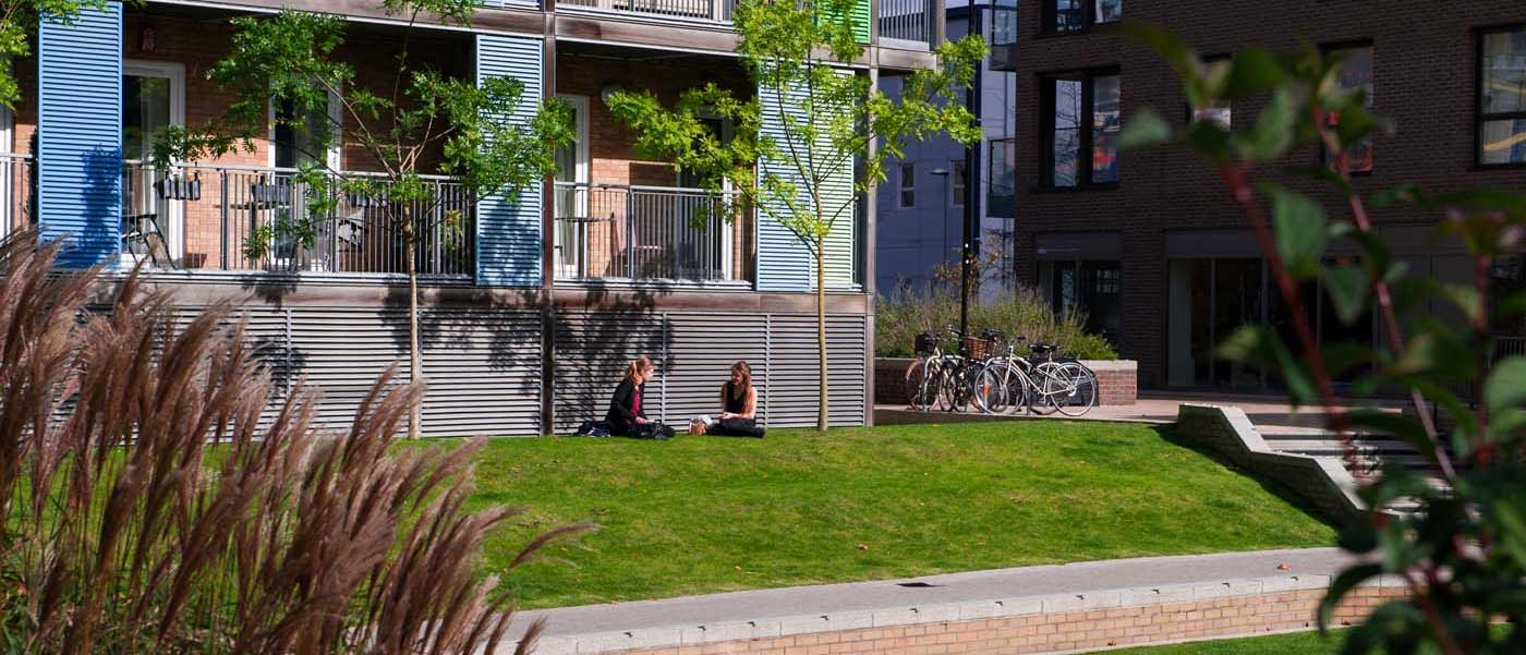Medium distance image of two female friends sitting on grass in Mill Park, CB1 in the sun