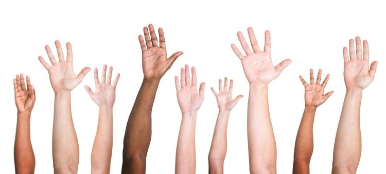 Row of upraised hands from people of different ethnicities signifying volunteering